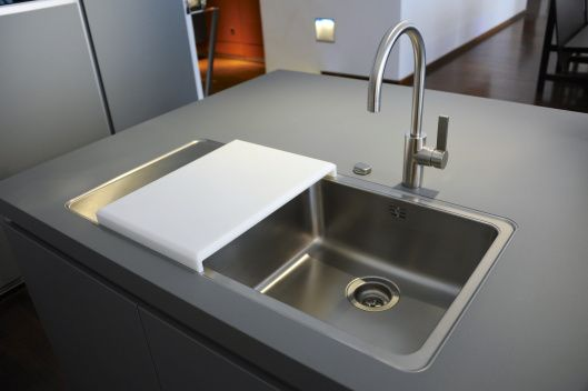 Sink with moveable cutting board