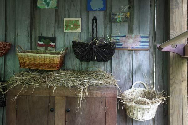 No coop is complete without nesting boxes and roosting perches. Inside this coop, sturdy wicker baskets padded with straw serve as cozy places for hens to lay their eggs, while a wood closet rod acts as a perch for sleeping. | Photo: Misty Keasler/Redux Pictures | thisoldhouse.com