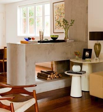 """Aparador moderno no lugar da antiga lareira de sua casa, a arquiteta Ana Marinho construiu um aparador de alvenaria que separa as salas de estar e jantar. Como já havia o assoalho de madeira, ela revestiu toda a estrutura (1,20 x 1,05 m) e a parede ao lado com cimento queimado. """"Em vez de eliminar a lareira, que não usava, criei um elemento que é decorativo e tem a função de apoio para a sala de jantar"""", diz. O acabamento, que mistura cimento com pó de mármore e resina, custou R$ 40 o m²…"""
