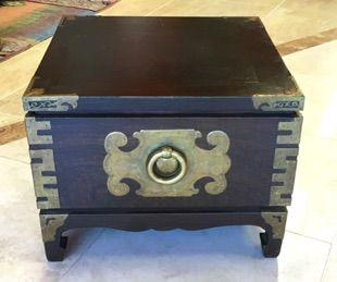 "Low Asian storage box and/or ottoman. Dark, grainy, wood (Chinese Elm) enhanced with brass mountings on edges and sides—including symbol for longevity. Put a pillow on the lid to make a seat or footstool. 18"" x 18"" x 14"""