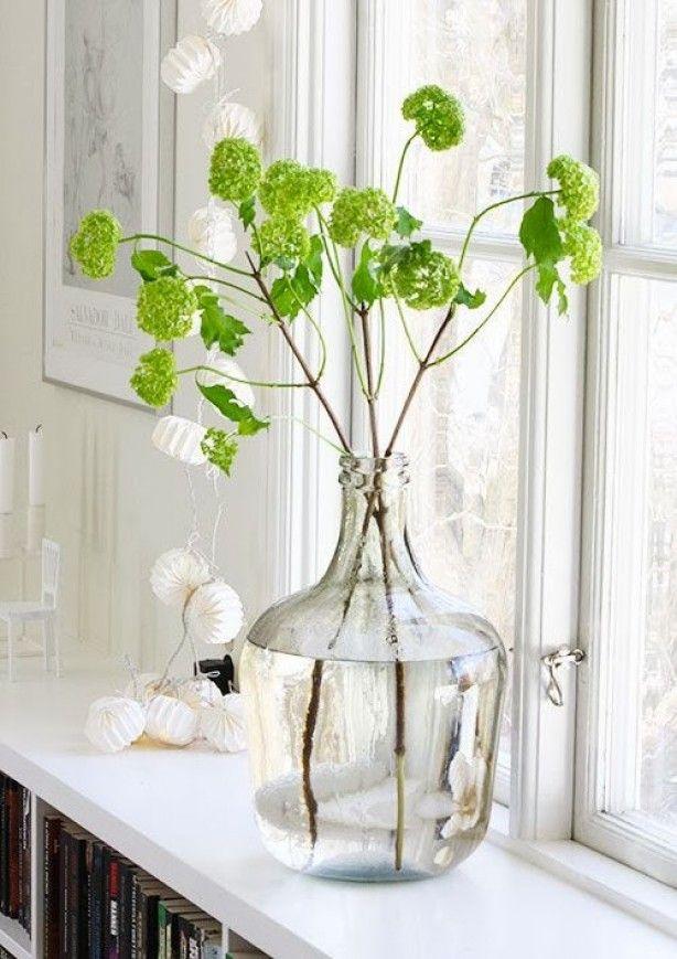 Vensterbank of dressoir idee: een glazen vaas met een simpele tak erin. Deze is heerlijk fris groen!