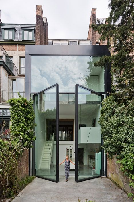 Sculpt IT adds the world's largest pivoting #window to an Antwerp home. The pair of glass panels, weighing almost four tons and spanning two stories in height, pivot out towards the garden of this renovated home.