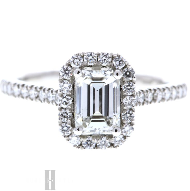 This dazzling ring features an impressive 1.06 carat emerald cut claw set diamond in a deco cluster style, on a platinum mount. With sparkling brilliant cut diamond halo, this ring is guaranteed to make an impression, perfect for when asking that all important question.