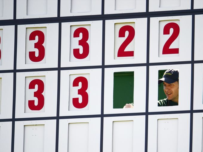 A course worker changes the scores during the second round of the 2014 Masters golf tournament at Augusta National Golf Club.