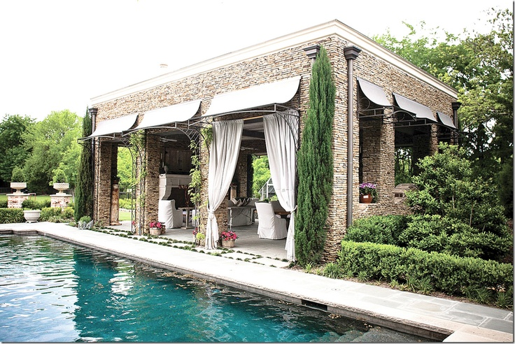 The pool cabana is made of stacked stone with columns.  Notice the gutters  and awnings.