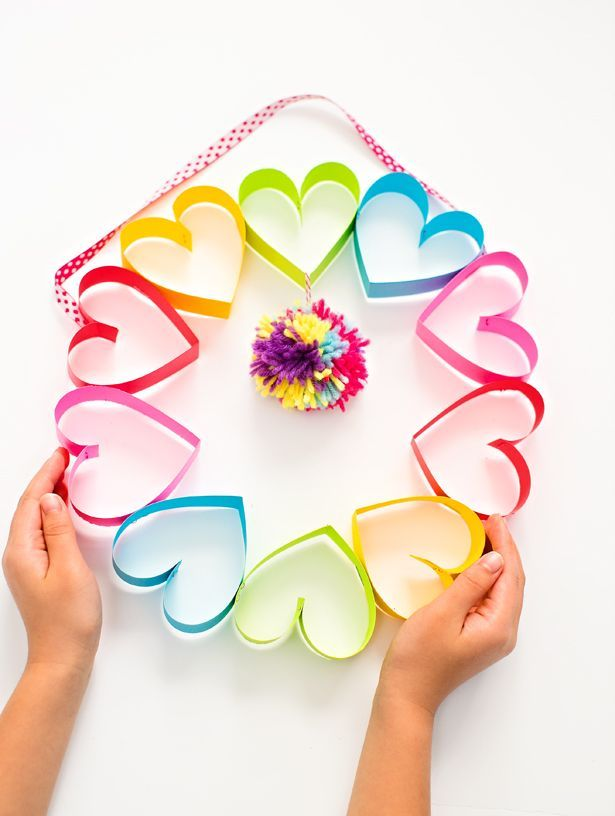 DIY RAINBOW PAPER HEART POM POM WREATH is a great craft for children to decorate for Valentines Day. #CraftyKids #Valentines #YakAcademyWorldLanguageClassForChildren