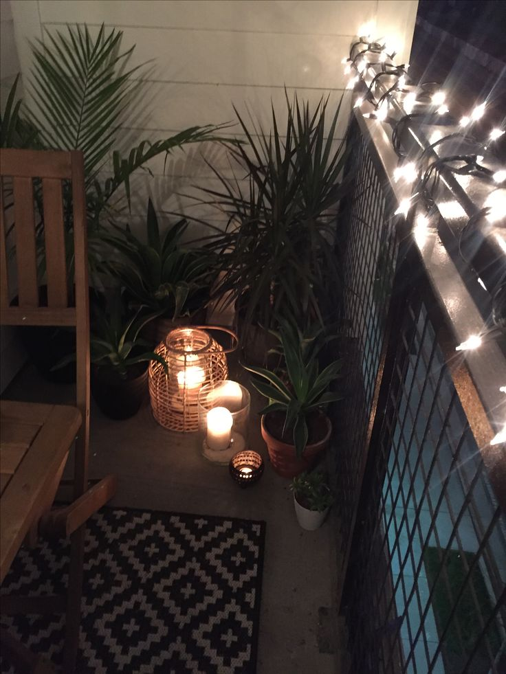 Tropical plants, candles, lanterns, string lights, small apartment balcony decor ideas. Perfect for hot summer nights outside and dining al fresco