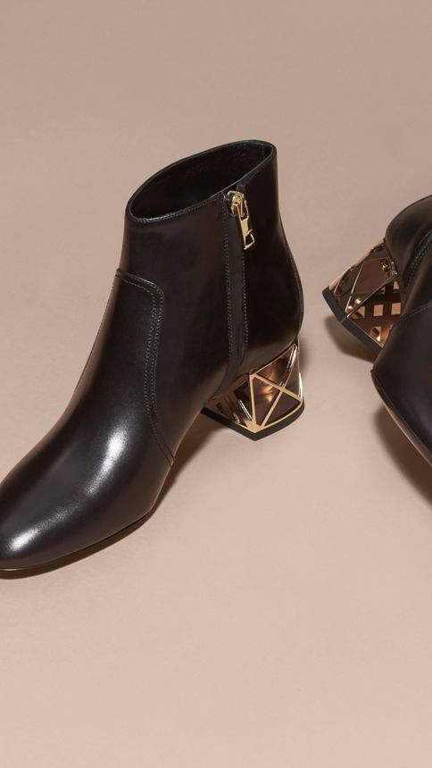 Leather Burberry ankle boots with accents of polished metal hardware, including a check-caged block heel. A soft accent to smart tailoring.