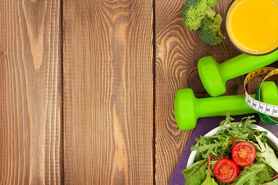 dumbbells, healthy food, and measuring tape comprise a fitness and health collage
