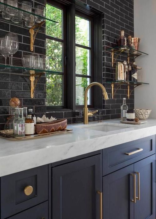 Dark cabinets dark subway backsplash floating shelves brass hardware marble countertops