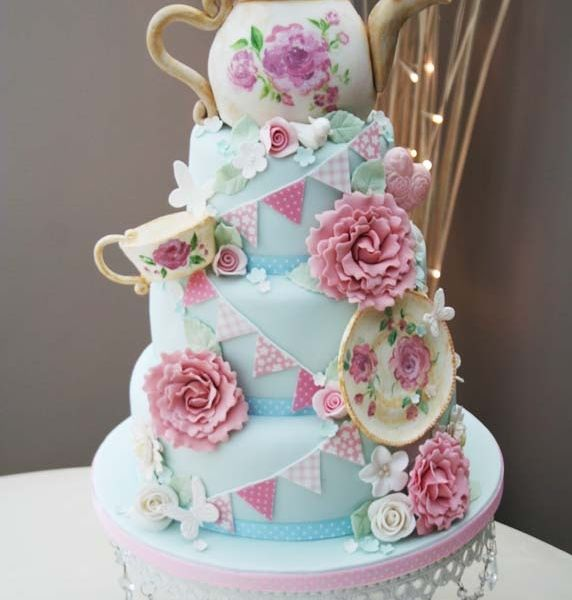 A teapot-themed cake with vintage flowers, bunting, and, of course, a teapot!