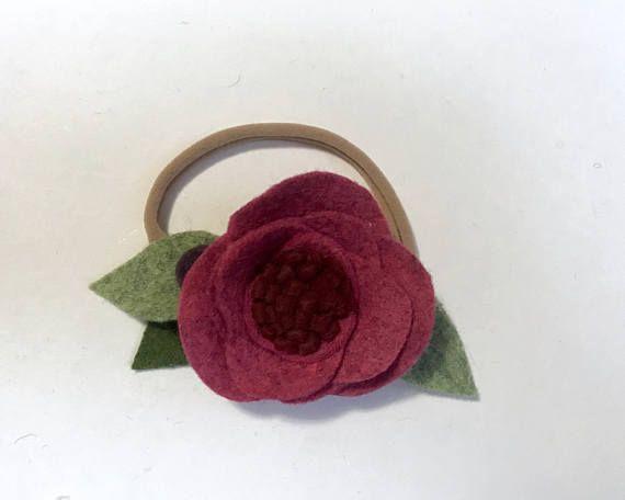 Escarlata es una flor de mezcla de lana rosa rubí profundo con centro rojo oscuro y bolas de lana Borgoña oscuro en las hojas.  Diademas de flores de todos son hechos a mano y creados de un fieltro de mezcla de lana de alta calidad y garantizada a una montura de nylon suave. Cada