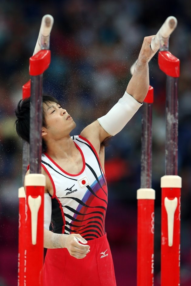 JULY 30: Kohei Uchimura of Japan puts chalk on the parallel bars in the Artistic Gymnastics Men's Team final on Day 3 of the London 2012 Olympic Games at North Greenwich Arena on July 30, 2012 in London, England. (Photo by Streeter Lecka/Getty Images)