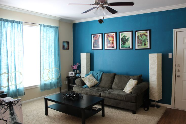 Teal accent wall with black and brown furniture for the - Grey and blue living room furniture ...