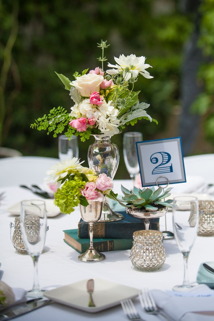 Vintage silver, milk glass and old book centerpieces. Flowers by @Flower Allie