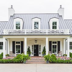 Home exterior design inspiration; white Hardie plank siding, black roof, black door, black shutters, black garage, thin pillars, dormers