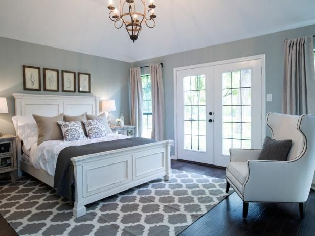 HGTV: Check out this newly redesigned master bedroom has dark wood floors, large windows and French doors with linen drapes and blue-gray walls from Fixer Upper.