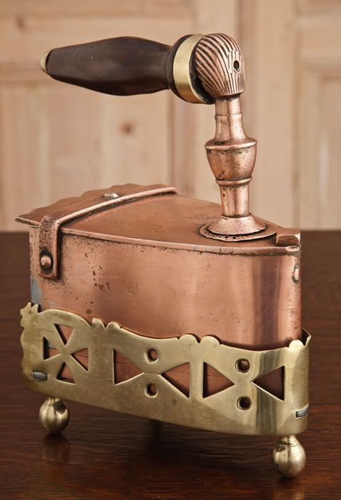 Antique Copper Clothes Iron with Brass Cradle.  Survived with its original brass cradle that protected tabletops and surfaces, this clothes iron would receive hot coals from the trapdoor at the rear. Copper was prized for its heat transfer characteristics which are still appreciated today. Wooden handle protects the user.   Circa 1870.