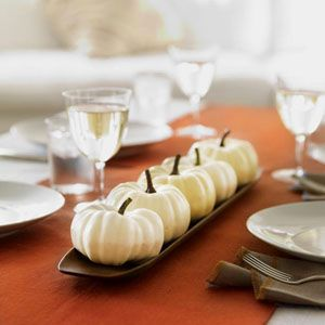 Seasonal simplicity doesn't get any speedier than this streamlined display: Just parade small white pumpkins along a wooden platter, and — to play up the gourds' paleness — add a runner or fabric remnant in autumnal orange. In five minutes, you're done.
