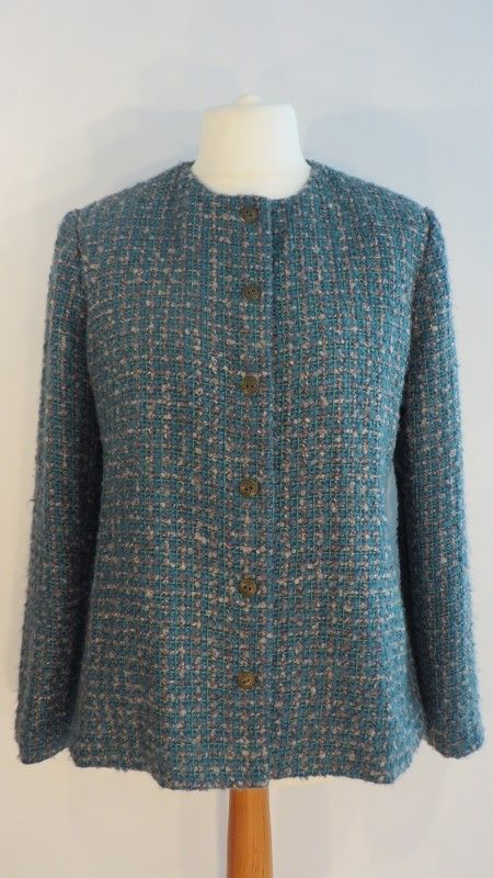 Vintage green & gold boucle jacket, 18.   Classic collarless sea green and old gold boucle jacket. It's wonderfully soft and has the most charming 'atom' like metal buttons (a spare is woven into the hem). Fully lined.   Size: 18 Measurements: B: 46, W: 45, H: 47, L: 26, S-S: 17 Label: None Decade: 1970 Material: Wool / polyester blend Cleaning instructions: Dry clean