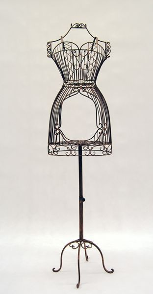 This Female Wire Dress Form is made from wrought iron and has its own display shelf and antique metal base. The form offers a versatile canvas to create decorative floral sculptures or on which to han