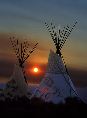 Sunrising between two tee pees at Taos Drum, Taos, New Mexico