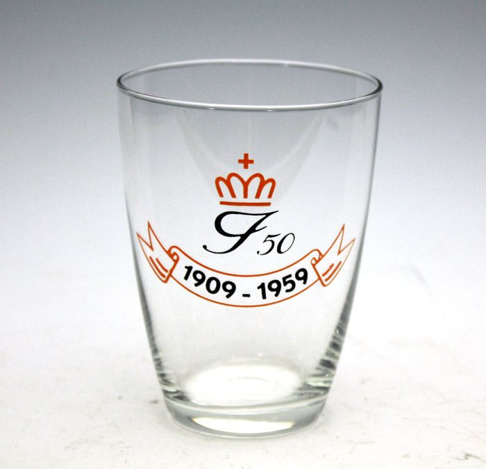 A. D. Copier - 50 jaar Juliana. 1959, Glasfabriek Leerdam Een blank glazen beker met zwart en oranje email beschildering. Ter gelegenheid van Juliana 50ste verjaardag. Hoogte 9,6 cm. Diameter 7 cm.