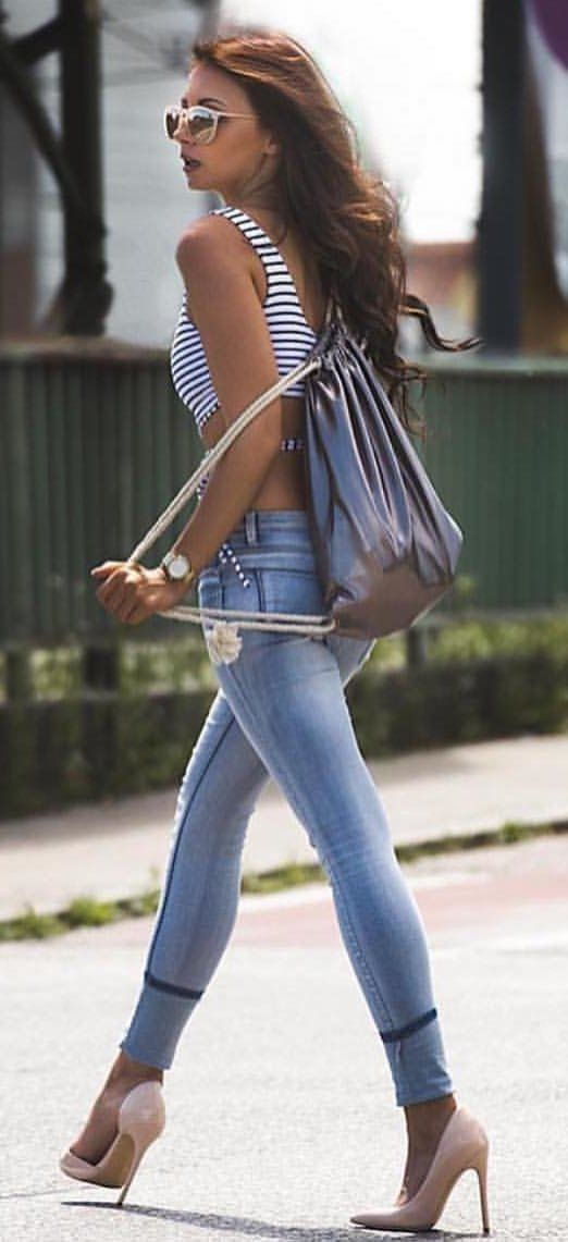 #spring #outfits woman in white and black striped sleeveless crop top, blue jeans, and pair of pink high-heels sandals walking across the street during daytime. Pic by @chicnchic_factory