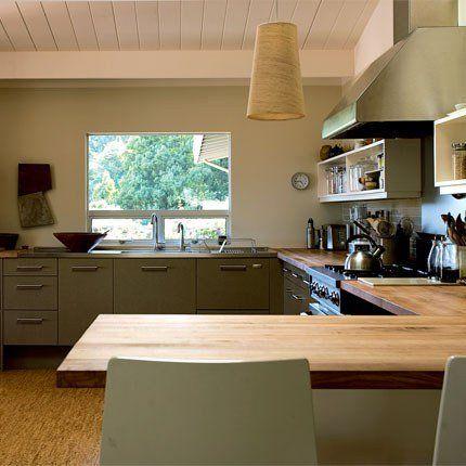 """Même si la couleur est un peu sombre, la disposition est idéale : double évier sous la fenêtre, probablement à coté du frigo, puis un mur """"cuisson"""" et enfin un plan de travail-bar qui vient séparer la cuisine du salon et autour duquel on peut venir s'asseoir à plusieurs"""