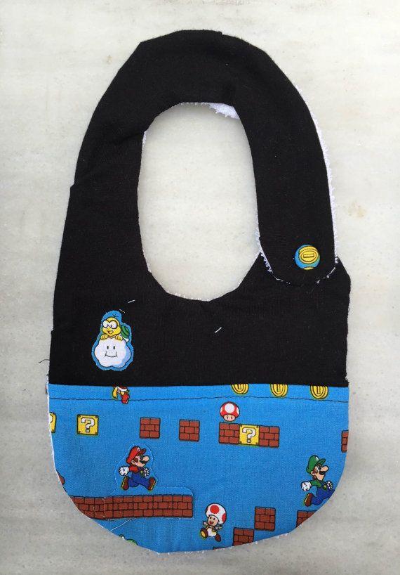 Original Babero hecho a mano con motivos del conocido videojuego de Super Mario. Está compuesto por una capa te tela de rizo impermeable blanca, una