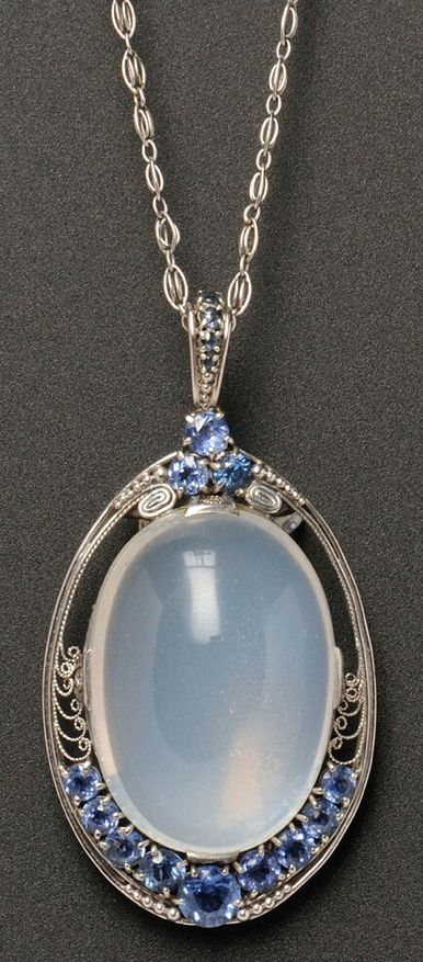 Arts & Crafts Platinum, Moonstone, and Sapphire Pendant, Tiffany & Co., set with a cabochon moonstone measuring approx. 30.00 x 20.40 x 12.20 mm, framed with Montana sapphires and scrolling wirework, suspended from a fancy link chain, lg. 2 1/4 and 21 in., signed