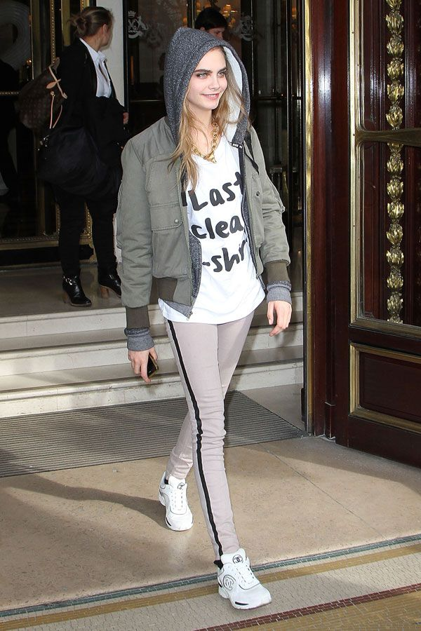 Cara Delevingne Keeps It Real. While she's got serious style in spades, it's no secret that Cara also has a keen sense of humor—the It girl isn't afraid to make a statement with whimsical accessories and footie pajamas, after all. No surprise, then, that she's rocking this funny top with aplomb.