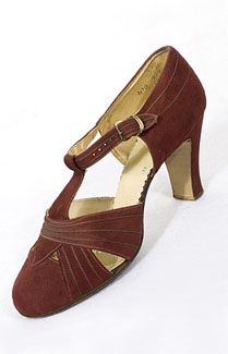 Suede T-strap shoes, c.1927-1933. The rising hemlines of the 1920s focused attention on the exposed leg and foot. By the late 1920s, heels were higher, and cutwork over the toes was popular. The fabulous T-strap shoes were then the acme of style. These knockout shoes are fashioned from burgundy suede and lined with tan kid. The cutwork areas and straps are decorated with narrow bands of matching top-stitched kid. The straps close with brass buckles. The Louis heels are high and slender.