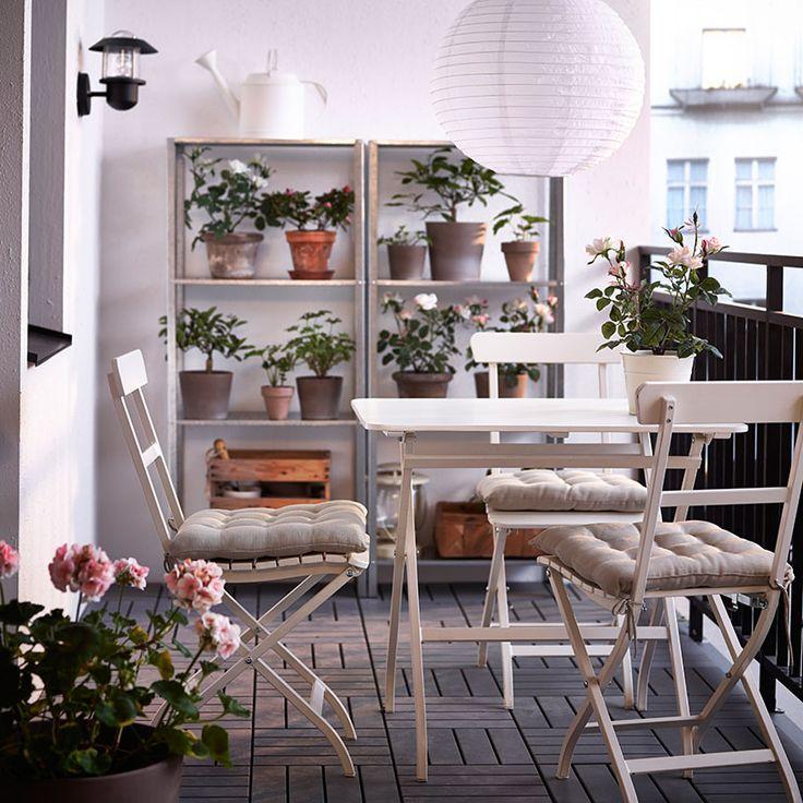Ein Balkon mit MÄLARÖ Tisch und Klappstühlen in Weiß, verzinkten Regalen und SOLVINDEN Solarleuchte in Weiß