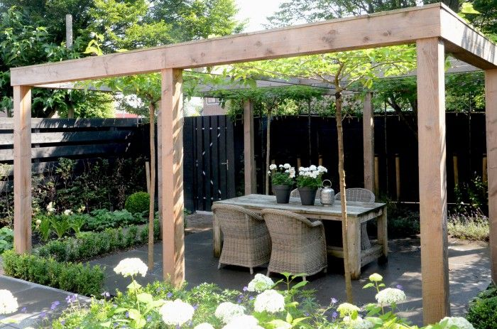 Strakke pergola & platanen zorgen voor schaduw & sfeer in de tuin.