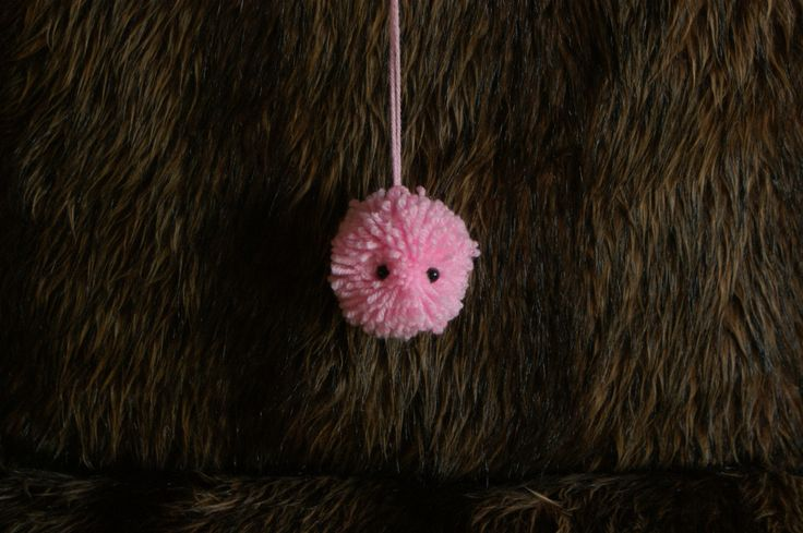 pom pom made out of woolstrings with eyes. perfect to do with childeren, you can also use different kind of colours for effects. All you need is wool,2 cartons in a round shape with a hole in them and some eyes.