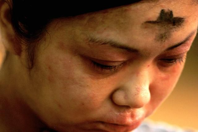 Catholic Calendar for Lent 2015: A woman prays after receiving ashes on her forehead in observance of Ash Wednesday at Saint Louis Cathedral, February 6, 2008, in New Orleans, Louisiana.