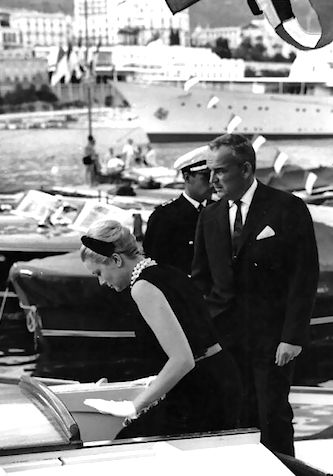 Princess Grace in a black sheath and pearls and Prince Rainier at a port in Monaco, 1962