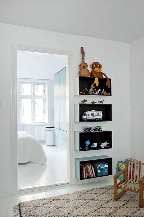 Bogkasserne på væggen i børneværelset er lavet i blågrønne nuancer, der matcher skabene i soveværelset. Børnestolen er fra Collect Furniture.