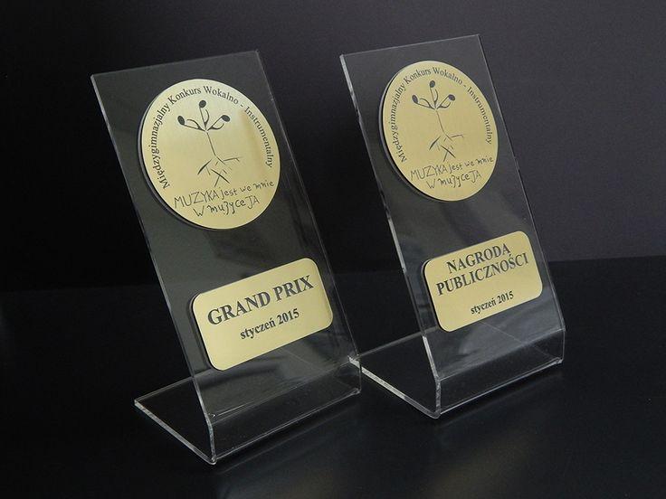 Statuetka pamiątkowa na Międzygimnazjalny Konkurs Wokalno-instrumentalny dla młodych muzyków. Do wykonania nagród wykorzystano pleksi bezbarwną i laminat grawerski w kolorze złotym.