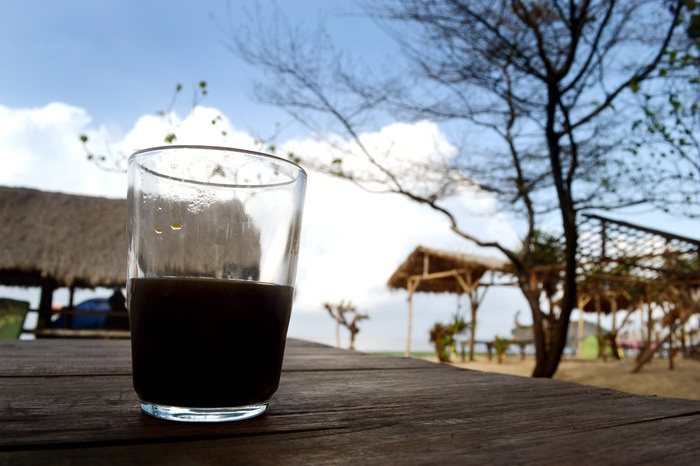 A glass of coffee bids a good morning to the peaceful beach. Photo by Stefanus Ajie.