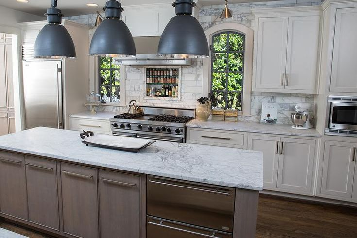 Amazing kitchen features three black industrial pendants illuminating a long and narrow taupe center island fitted with stacked dishwasher drawers topped with white marble.