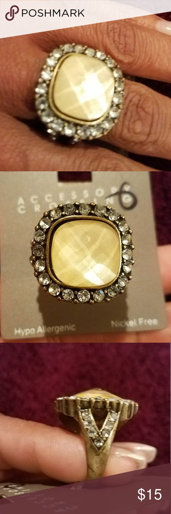 NWOT. Boutique costume jewelry ring NWOT. Costume jewelry ring. Light yellowish color stone with accent looking rhinestone around it. Also has accent looking rhinestones on V-style sides of the ring. Boutique Jewelry Rings