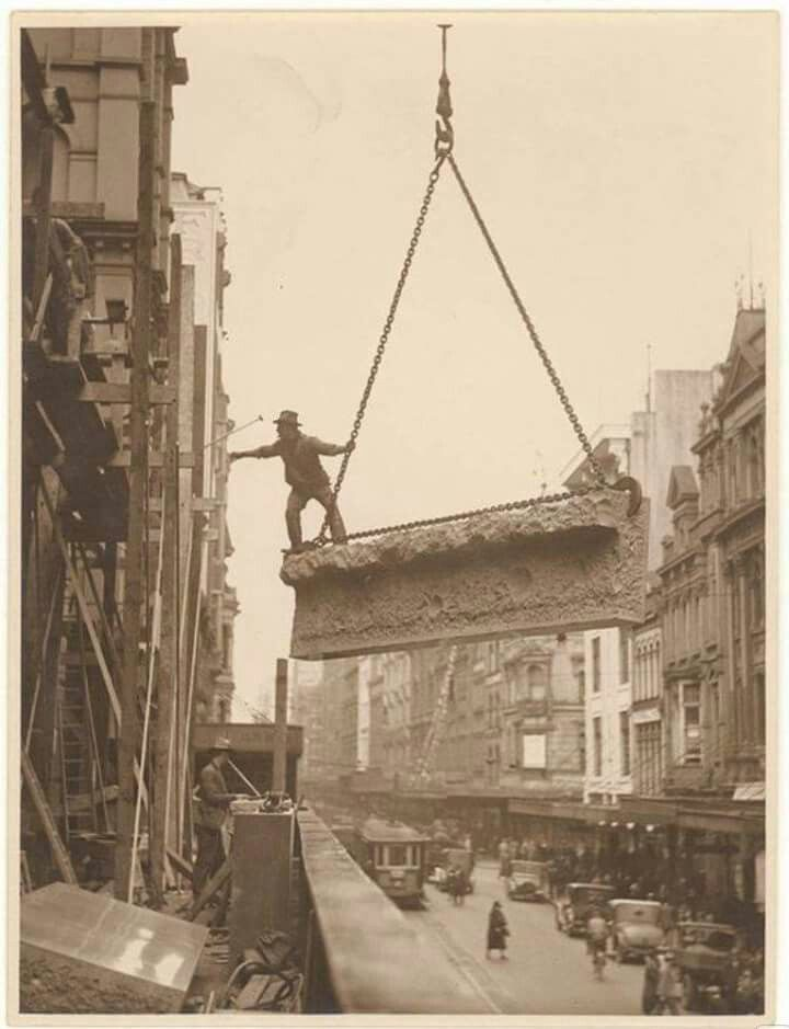 A building labourer is on a stone being hoisted up to building,Pitt St, Sydney in the 1930s. State Library of NSW.