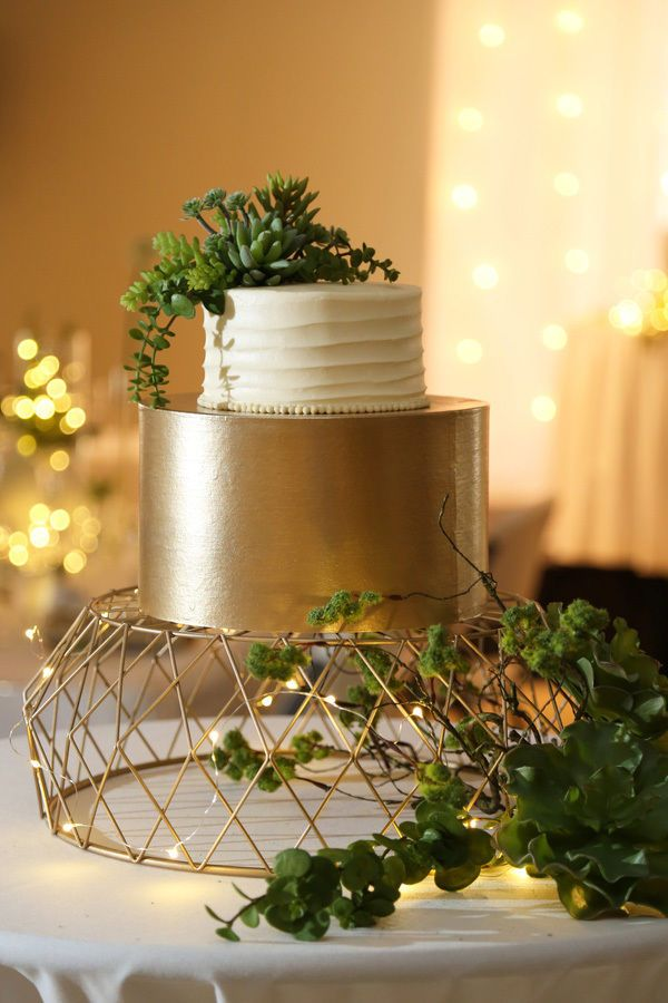 A white and gold wedding cake with metallic gold fondant layer on bottom tier, white buttercream layer on top tier, green succulent topper, and geometric wire gold cake plate.