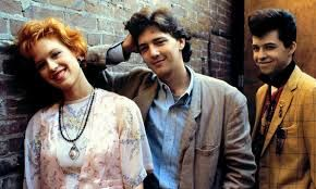 """Pretty in Pink is a 1986 American romantic comedy film about love and social cliques in American high schools in the 1980s. A cult classic, it is commonly identified as a """"Brat Pack"""" film. It was directed by Howard Deutch, produced by Lauren Shuler Donner, and written by John Hughes, who also served as co-executive producer."""