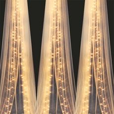 Glowing Curtains A little lace or sheer panel and christmas lights or rope lights should do the trick