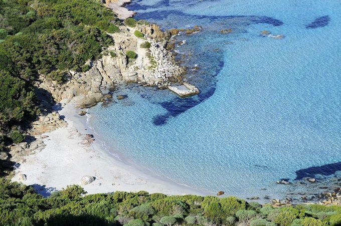 """SPIAGGIA DEI DUE MARI, PORTO GIUNCO, VILLASIMIUS – CAGLIARI – SARDEGNA Un fondo morbido di sabbia finissima, dalle opalescenze rosate, e un mare cristallino, in cui restare a mollo per ore, sotto i dolci e tenaci raggi del sole della Sardegna. La """"Spiaggia dei due mari"""" è così chiamata perché divide il mare, dallo stagno di Notteri, dove è possibile avvistare i bellissimi fenicotteri rosa. Si tratta di una lunga lingua di sabbia bianca con due insenature naturali ad accrescerne la bellezza"""