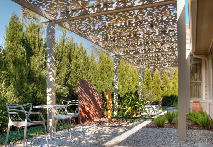 Pergola aus Lochblech wirft Schatten über der Terrasse mit Kiesboden