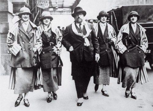 """Tijdens de roerige jaren twintig stond Chanel bekend als de 'Koningin van de Mode'. """"Elegant zijn is geen kwestie van een nieuwe jurk aantrekken. Je bent elegant, omdat je elegant bent."""" In 1918 kreeg ze een gebouw aan de 31 rue Cambon in Parijs in handen. In 1921 opende zij haar eerste """"modeboetiek"""" en verkocht hier kleding, hoeden en accessoires. In 1927 bezat ze vijf gebouwen aan de Rue Cambon, namelijk nummer 23 tot 31. Zij was degene die de Garçonne-stijl bedacht: ze trok vrouwen truien…"""
